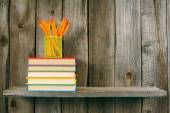 Books and pencils on a wooden shelf. — Stock Photo