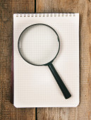 Notebook and magnifier on wooden background. — Zdjęcie stockowe