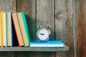 Alarm clock and books on wooden shelf. — Stock Photo