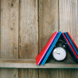 Alarm clock and writing-books on a wooden shelf. — Stock Photo #52155827