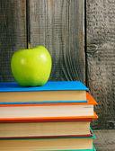 Multi-coloured books and green apple . — Foto de Stock