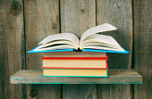 The open book on a pile from books. — Stock Photo