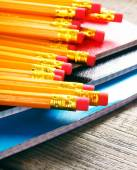 Pencils and writing-books. On wooden background. — Stock Photo
