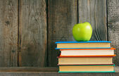 Multi-coloured books and green apple . — Stock fotografie