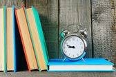 Alarm clock and books on a wooden shelf. — Stock Photo