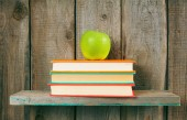 Apple and books on a wooden shelf. — Stock Photo