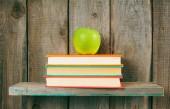 Elma ve bir ahşap raf kitaplar. — Stok fotoğraf