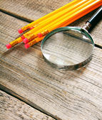 Magnifier and pencils. On wooden background. — Stock Photo