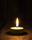 Burning candle. On wooden background. — Stock Photo