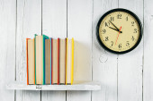 Watches and books on a wooden shelf. — Stock Photo