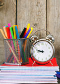Writing-books, an alarm clock and school tools. — Stock Photo