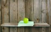 Apple and writing-books on a wooden shelf. — Stock Photo