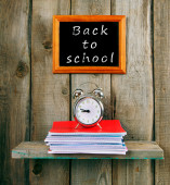 Back to school. An alarm clock and writing-books — Stock Photo