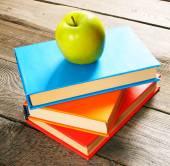 Pomme verte et livres. sur le fond en bois. — Photo