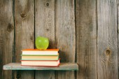 Apple and books on a wooden shelf. — Stockfoto
