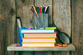Books and school tools on a wooden shelf. — Stockfoto