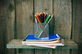Writing-books and school tools on a wooden shelf. — Stock Photo