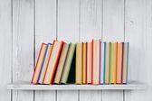 βιβλία σε ένα ξύλινο ράφι. — Φωτογραφία Αρχείου