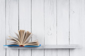 The open book on a wooden shelf. — Stock Photo
