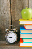 Alarm clock, green apple and books. — Stock Photo
