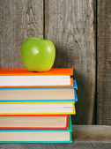Multi-coloured books and green apple . — Stock Photo