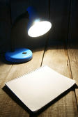 Notebook and the fixture. On wooden background. — Stock Photo