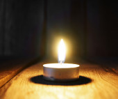 Burning candle. On wooden background. — Stock Photo