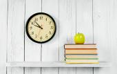 Watches, books and a green apple on wooden shelf. — Stock Photo