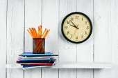 Watches, writing-books and school tools on a wooden shelf. — Stock Photo