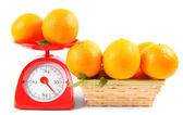 Oranges on scales and in a basket — Stock Photo