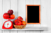 Apples on scales and in a basket — Stock Photo