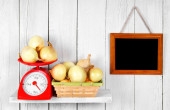 Onions on scales and in a basket — Stock Photo
