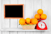 Orange on scales and in a basket — Stock Photo