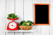 Cucumbers on scales and in a basket — Stock Photo