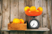 Oranges on scales and in box — Stock Photo