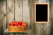 Tomatoes in an old box on a wooden shelf. — Stock Photo