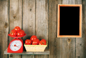 Tomatoes on scales and in a basket — Stock Photo
