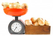 Onions on scales and in a box — Stock Photo