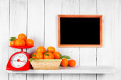 Tangerines on scales and in a basket — Stock Photo