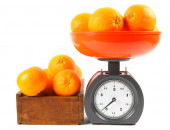 Oranges on scales and in a box — Stock Photo