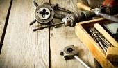 Stará vrtačka, box s vrtáky, kleště a vládce na dřevěné pozadí. — Stock fotografie