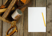 Paper with pencil and old tools in box on wooden background. — Stock Photo