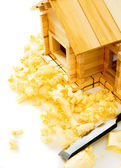 House construction. Joiners works. The wooden house, chisel and shaving on white background. — Stock Photo