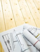 Many drawings for building on a wooden background. — Stock Photo