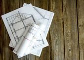 Many drawings for building on old wooden background. — Stock Photo