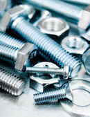 Nuts, screws and bolts on scratched metal background. — Stock Photo