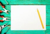 Paper with pencil and the working tools on wooden, green background. — Stock Photo