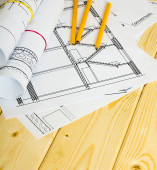 Many drawings for building and pencils on a wooden background. — Stock Photo