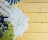 Repair work. Drawings for building, gloves, glasses and others tools on wooden background. — Stock Photo