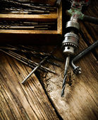 Old drill, box with drills on wooden background. — Stock Photo